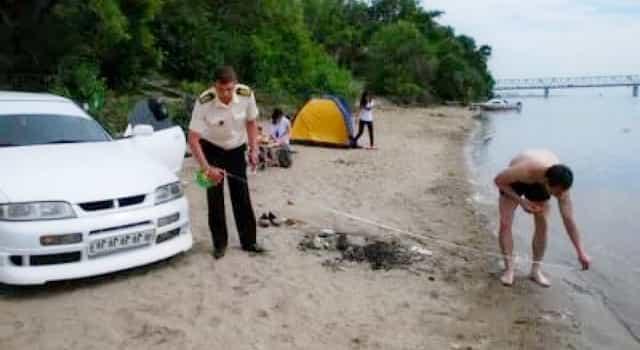 Инспектор Рыбоохраны измеряет расстояние от машины до границы воды - протокол по статье 65 ВК РФ